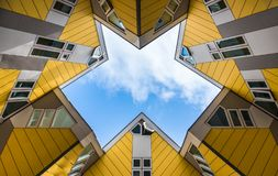 Simmetry Gleam between Yellow Cubic houses and apartments in Rotterdam. The Netherlands. Simmetry Gleam of cloudy sky between Yellow Cubic houses and apartments royalty free stock photo