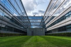 Free Simmetry In Modern Architecture. Reflection Of Clouds In Glass Windows And Green Lawn In Front. Technical University Of Stock Photos - 127724093