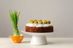 Simnel, english Easter cake in white stand and bright green gras Stock Photography