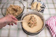 Simnel-Kuchen traditioneller Kuchen Briten Ostern, Hand, die mehr Kuchenmischung addiert Lizenzfreies Stockfoto