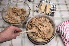 Simnel-Kuchen traditioneller Kuchen Briten Ostern mit der Hand, welche herein die Mischung setzt Lizenzfreie Stockfotos
