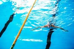 Simning för hög man i en inomhus simbassäng fotografering för bildbyråer