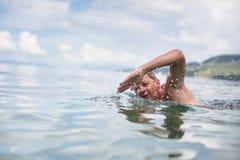 Simning för hög man i havet/havet arkivfoton