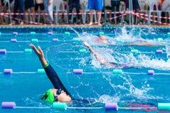 Simning för tillbaka slaglängd för unga simmare praktiserande på en lokal swimmi arkivbild
