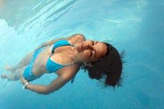 Simning för ung kvinna i en pöl med den blåa baddräkten arkivbilder