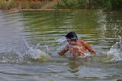 simning för ung man i dammet eller pölen på en sommarmiddag Sommarsimning spela med vatten i sommars?song arkivbilder