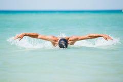 Simning för ung man i havvatten Arkivfoton