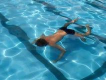 Simning för ung man i pölen Sikt från baksida royaltyfria bilder