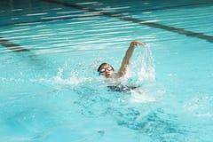Simning för ung man i ryggsim Arkivfoto