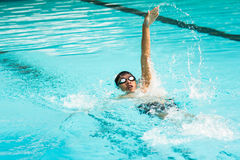 Simning för ung man i ryggsim Arkivbild
