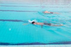 Simning för ung man i simbassängen Färdig simmareutbildning i simbassängen royaltyfria bilder
