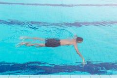 Simning för ung man i simbassängen Färdig simmareutbildning i simbassängen royaltyfri bild