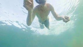Simning för ung man i snorkelmaskering och rör- och skytteselfievideo Ståendeman som under snorklar i maskering och snorkel stock video