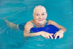 Simning för gammal kvinna med kickboard i pöl Royaltyfri Fotografi