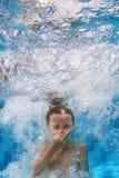 Simningbarnet hoppar undervattens- i den blåa pölen med färgstänk Royaltyfri Foto