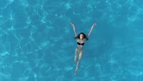 Simningflickan i swimwear kopplade av i klar pöl på sommartid, flyg- sikt lager videofilmer