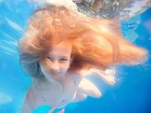 Simningung flicka med långt haired undervattens- i pöl Arkivfoto