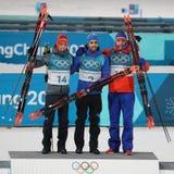 Simon Schempp GER l, Мартин Fourcade FRA и Emil Hegle Svendsen НИ на торжестве места старта ` s 15km людей биатлона массовом Стоковое Изображение