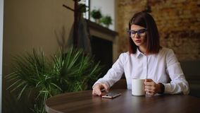 Simpatic brunette with glasses close-up. Drinks fragrant coffee and using a mobile phone dials up text messages, watches. News, flips through photos stock video footage
