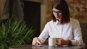 Simpatic brunette with glasses close-up. Drinks fragrant coffee and using a mobile phone dials up text messages, watches. News, flips through photos stock footage