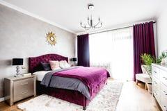 Simpl sovruminre med dubbelsäng, purpurfärgad sängkläder och moderna nightstands Royaltyfri Foto