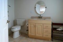 Simple apartment bathroom. Looking n through doorway to bathroom showing toilet and vanity Stock Photos