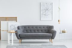 Artistic living room interior. Simple, artistic living room interior with a white map poster hanging above a gray sofa Stock Photo