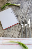 Simple background for menu with cutlery, onions and notepad Royalty Free Stock Photos