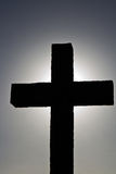 Simple backlit cross. Silhouette of a sturdy cross, with halo from the sun Royalty Free Stock Photos