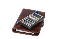 Simple ball-point pen, calculator and notebook. In leather cover on a white background Stock Images