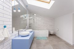Simple bathroom in attic. Simple bathroom in the attic with blue washbasin cabinet, toilet and bathtub against white brick wall royalty free stock photos