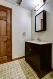 Simple bathroom interior with black cabinets and white sink. Simple bathroom interior with black cabinets, tile floor and white sink Royalty Free Stock Photo
