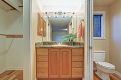 Simple bathroom interior with vanity cabinet and granite counter top. Hardwood floor Stock Images