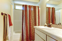 Simple bathroom with red and browns colors in shower curtain and Stock Photo