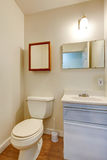 Simple bathroom with small washbasin cabinet and mirror. Simple bathroom with small light blue washbasin cabinet, mirror and toilet. Northwest, USA Royalty Free Stock Photography