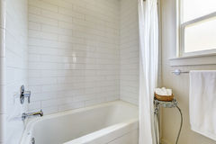Simple bathroom with tile wall trim and bath tub. White curtains and stand with wicker basket for towels Stock Images