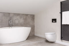 Simple bathroom with toilet. White bathtub against grey glaze in simple bathroom with toilet and black heater on white wall stock images