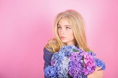 Simple beauty. Girl cute blonde hug hydrangea flowers bouquet. Natural beauty concept. Skin care and beauty treatment stock photography