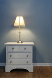 Simple Bedroom. Simple nightstand against blue wall with white trim and hardwood flooring Stock Image