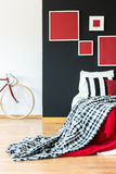 Simple bedroom of biker. Contrast colored walls in a simple bedroom of biker with a king-size bed and patterned blanket royalty free stock photography