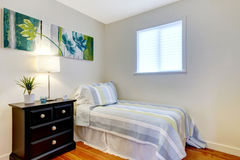 Simple bedroom with black nightstand and painting. Simple bedroom with black nightstand and small bed Stock Image