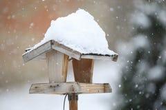 Simple bird feeder in winter garden. Simple homemade wooden bird feeder, birdhouse installed on winter garden in snowy day royalty free stock photo
