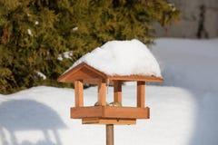 Simple birdhouse in winter garden. Simple homemade wooden birdhouse installed on winter garden in snowy day royalty free stock photos