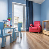 Simple blue baby room. With cot, armchair, balcony, window, small table and chairs royalty free stock photography