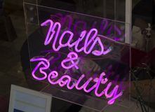 A simple blue neon advertising sign saying nails and beauty at the entrance to a manicure parlour Stock Photography
