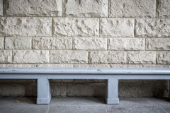 Simple blue wood bench. In front of a sand stone wall stock images