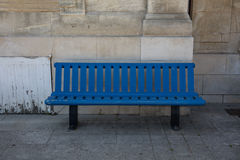 Simple blue wood bench in front of a sand stone wall. Blue wood bench in front of a sand stone wall stock photography