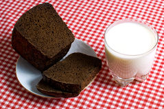 Simple breakfast. Glass of milk and black bread on a red tablecloth Stock Photo