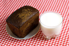 Simple breakfast. Glass of milk and black bread on a red tablecloth Royalty Free Stock Photos