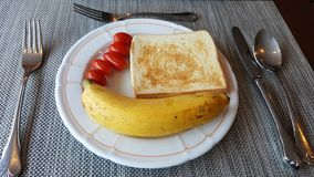 Simple breakfast with bread, banana and tomato. royalty free stock photos
